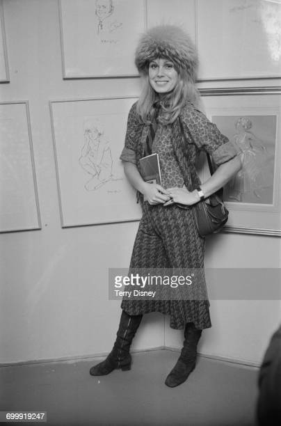 Actress Joanna Lumley stands by a drawing of herself by Trevor Willoughby at a Royal Academy exhibition of 'Stars on Canvas' London UK 21st October...