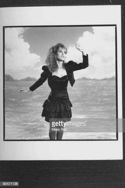 Actress Jodi Benson posing in front of an ocean scene backdrop as the voice of the mermaid Ariel for the movie The Little Mermaid