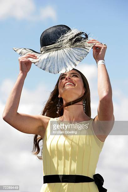 """Actress Jolene Anderson adjusts her hat at the """"Fashions on the Field"""" competition Nina Egan and Angela Menz and Ayshe Irdem pose together during the..."""