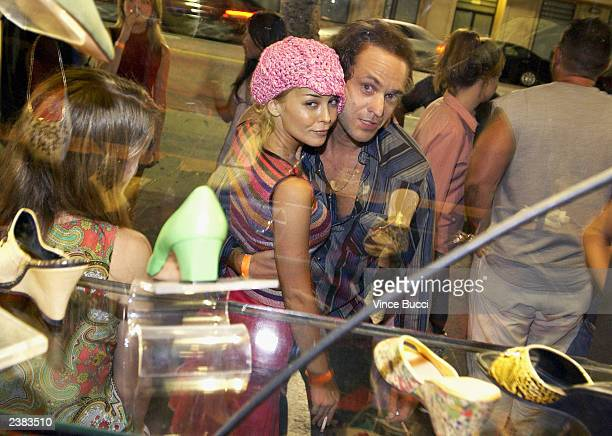 Actress Jordan Ladd and actor Arie Verveen look into a display window at the afterparty for the premiere of the film Cabin Fever on August 8 2003 at...