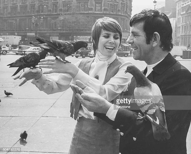 Actress Judy Carne and comedian Norman Wisdom feeding pigeons in Trafalgar Square as they promote their film 'All The Right Noises' London May 12th...