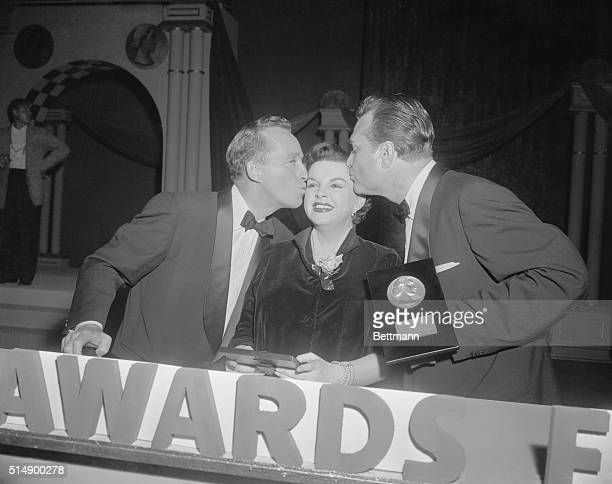 Actress Judy Garland is kissed by Bing Crosby and Red Skelton after she and Bing received the 1955 Look magazine awards for the best actress and...