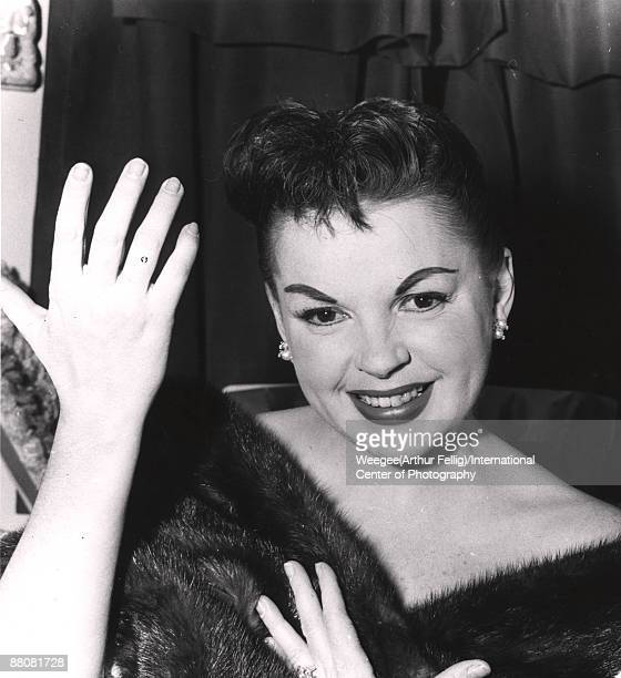 Actress Judy Garland smiles while holding her hands up, ca.1960s.