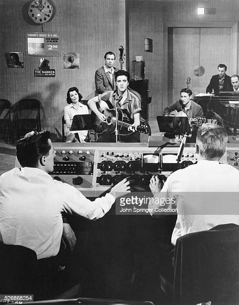 Actress Judy Tyler musician Bill Black on bass and musicians Elvis Presley and Scotty Moore on guitar in a recording studio with sound technicians in...