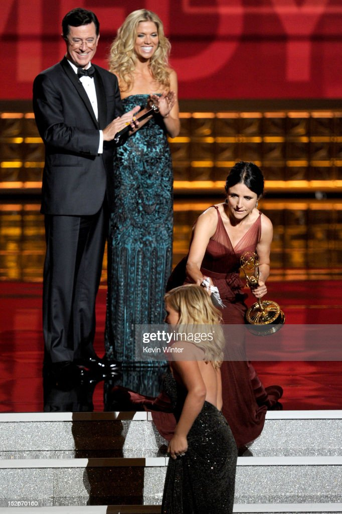 Actress Julia Louis-Dreyfus (R) accepts Outstanding Lead Actress in a Comedy Series award for 'Veep' from presenters Stephen Colbert and Amy Poehler (below) onstage during the 64th Annual Primetime Emmy Awards at Nokia Theatre L.A. Live on September 23, 2012 in Los Angeles, California.