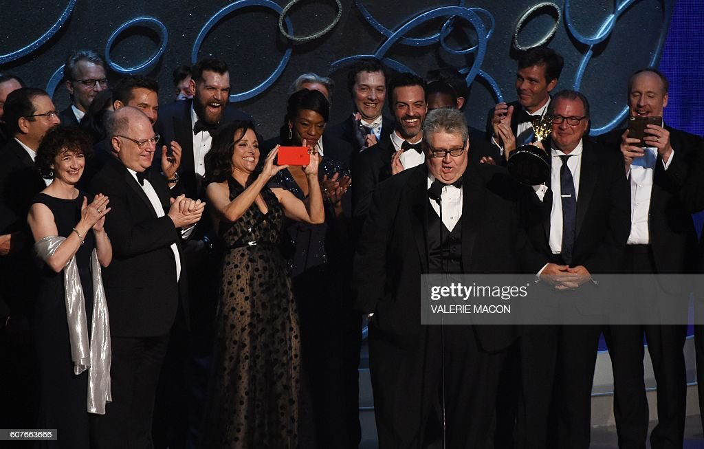 TOPSHOT - Actress Julia Louis-Dreyfus (center L) and producer David Mandel (4R) and the cast and crew accept the award for Outstanding Comedy Series for 'Veep' during the 68th Emmy Awards show on September 18, 2016 at the Microsoft Theatre in downtown Los Angeles. / AFP / Valerie MACON