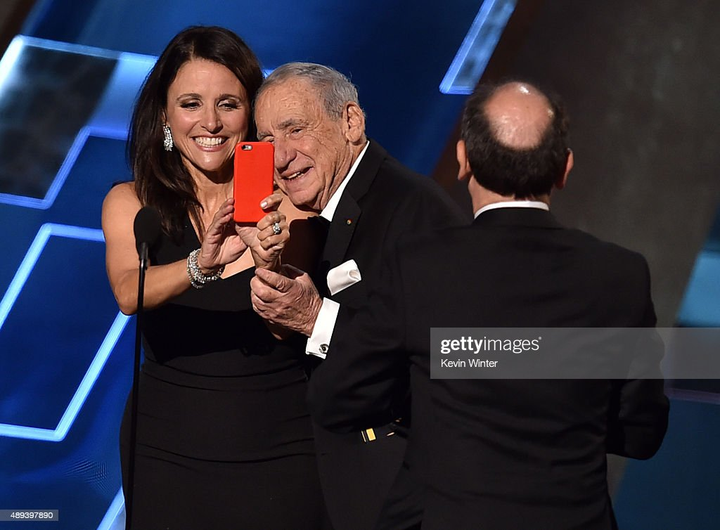 Actress Julia Louis-Dreyfus (L) takes a selfie with presenter Mel Brooks as she accepts Outstanding Comedy Series award for 'Veep' onstage during the 67th Annual Primetime Emmy Awards at Microsoft Theater on September 20, 2015 in Los Angeles, California.