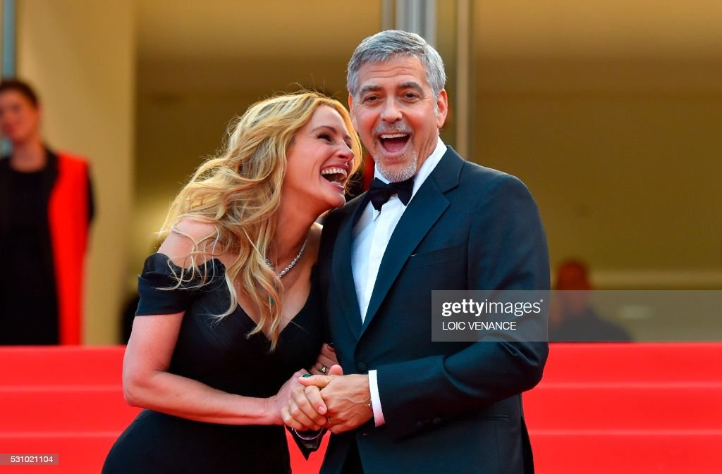 TOPSHOT - US actress Julia Roberts laughs on May 12, 2016 with US actor George Clooney as they arrive for the screening of the film 'Money Monster' at the 69th Cannes Film Festival in Cannes, southern France. /