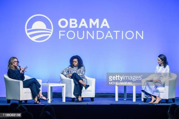 Actress Julia Roberts speaks as former US first lady Michelle Obama listens as they attend an event for the Obama Foundation in Kuala Lumpur on...