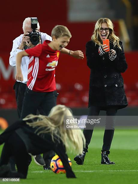 Actress Julia Roberts takes photos of her children on the pitch after the Premier League match between Manchester United and West Ham United at Old...