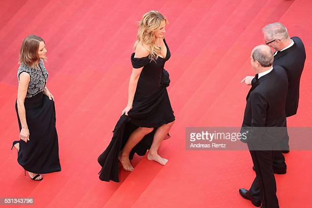 Actress Julia Roberts walks barefoot upon her arrival as producer Jodie Foster smiles at the 'Money Monster' premiere during the 69th annual Cannes...