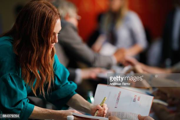Actress Julianne Moore signs autographe to fans during 'Wonderstruck' Press Conference during the 70th annual Cannes Film Festival at Palais des...