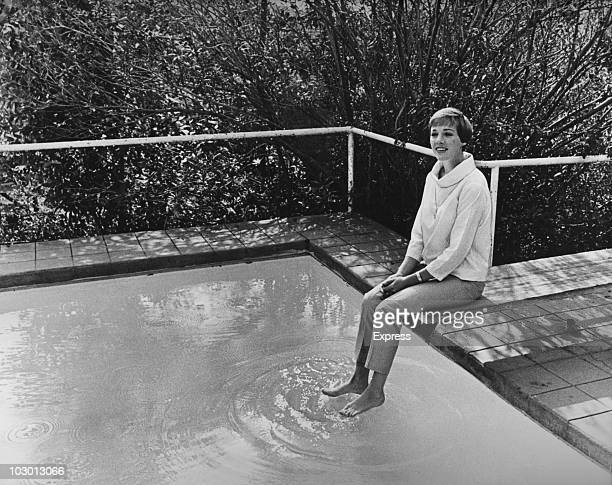 Actress Julie Andrews sitting on the edge of a swimming pool with her bare feet in the water in Hollywood California USA 9th November 1964