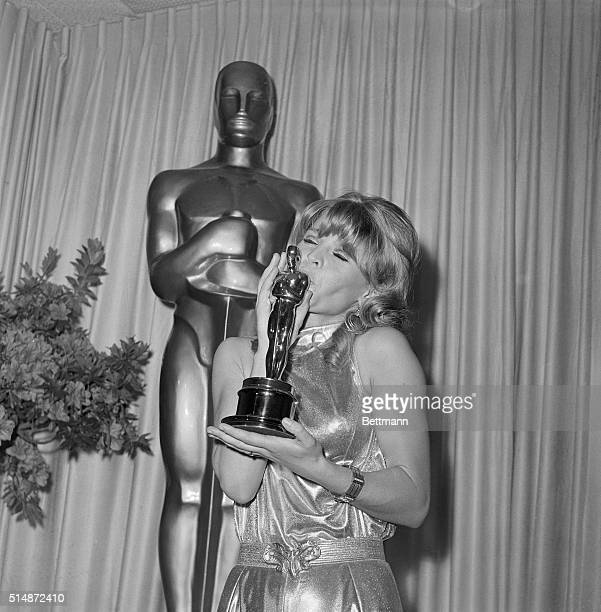 Actress Julie Christie kisses the Best Actress Oscar she won at the 38th Annual Academy Awards for her performance in the movie Darling