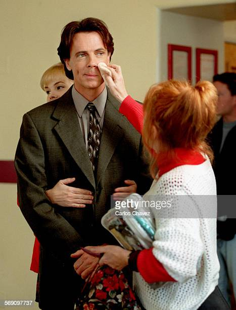 Actress Julie McCullough holds on to actor Rick Springfield as he is prepared for a taping of High Tide at Camarillo State Hospital