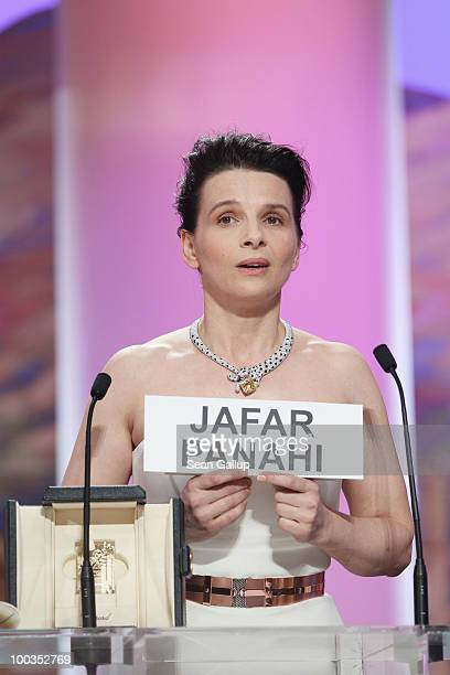 Actress Juliette Binoche holds a sign reading the name of Iranian director Jafar Panahi after winning the Best Actress award for her role in...