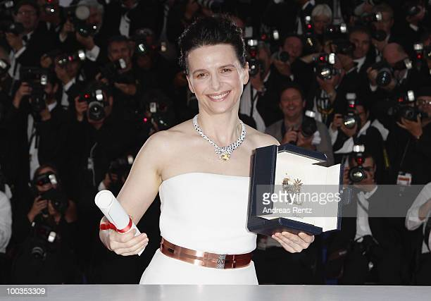 Actress Juliette Binoche poses with her Best Actress award for her role in Certified Copy at the Palme d'Or Award Ceremony photocall held at the...