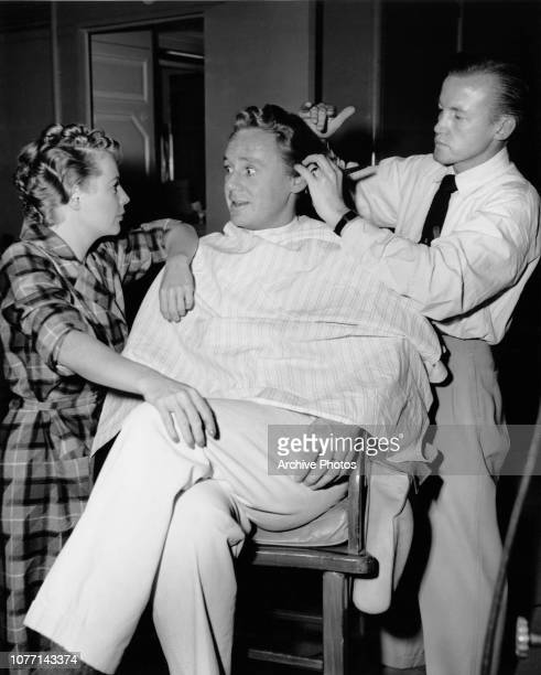 Actress June Allyson watches her costar Van Johnson having his hair cut by studio stylist John Truwe on the set of the MGM film 'Remains to be Seen'...