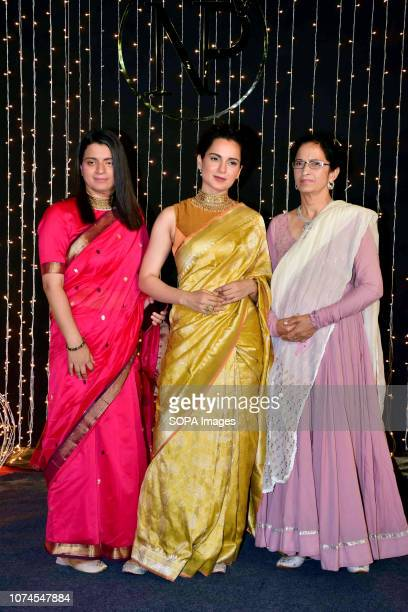 Actress Kangana Ranaut with mother Asha Ranaut and sister Rangoli pose as they arrive to attend PriyankaNicks wedding reception at hotel Taj Lands...
