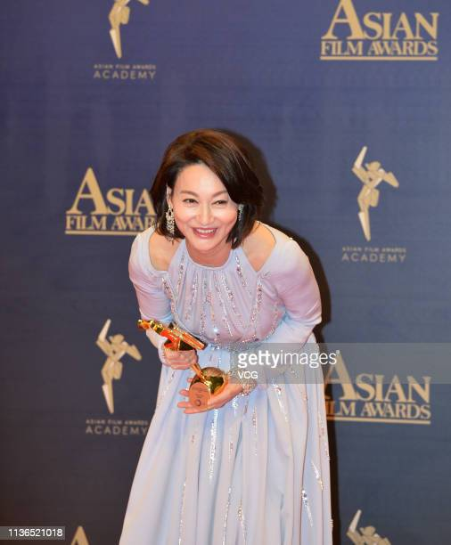 Actress Kara Hui Yinghung poses with the trophy backstage after winning the Best Supporting Actress during the 13th Asian Film Awards on March 17...