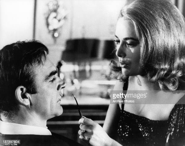 Actress Karin Dor has a sharp utensil up to Sean Connery's face in a scene from the film 'You Only Live Twice' 1967