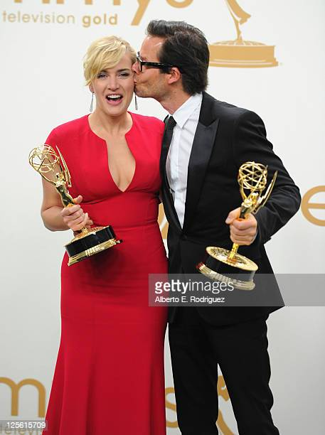 Actress Kate Winslet and actor Guy Pearce pose in the press room during the 63rd Annual Primetime Emmy Awards held at Nokia Theatre LA LIVE on...