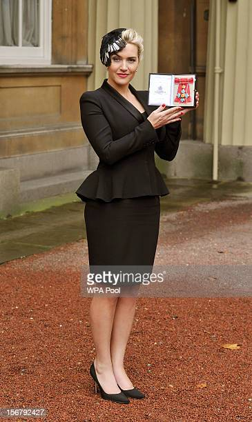 Actress Kate Winslet holds her CBE, for services to drama, which was awarded to her by Queen Elizabeth II during an Investiture ceremony at...