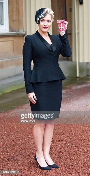 Actress Kate Winslet holds her CBE for services to drama which was awarded to her by Queen Elizabeth II during an Investiture ceremony at Buckingham...