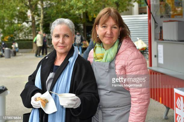 Actress Katerina Jacob and Marlies Brunner distribute hot meals to needy people organized by the local Caritas association Saint Korbinian Kitchen on...