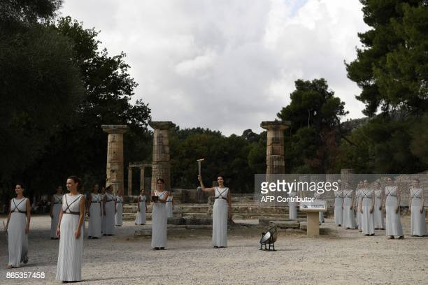 Actress Katerina Lechou acting the high priestess holds the Olympic flame at the Temple of Hera on October 23 2017 during a dressed rehearsal of the...