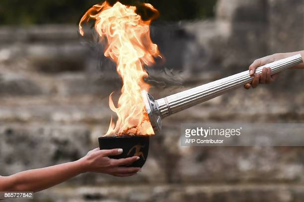 TOPSHOT Actress Katerina Lechou acting the high priestess lights the Olympic flame at the Temple of Hera in Olympia the sanctuary where the Olympic...