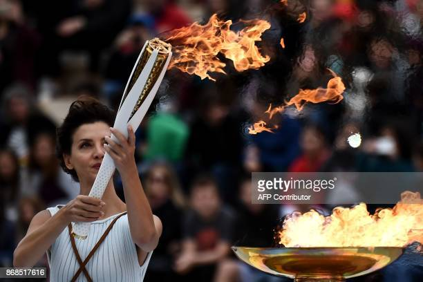 Actress Katerina Lechou performing a high priestess lights a torch at The Panathenaic Stadium in Athens on October 31 during the handover ceremony of...