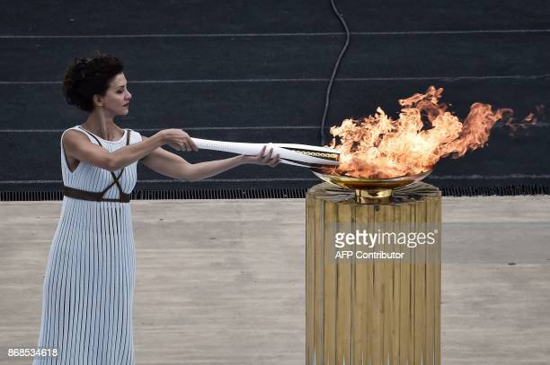 TOPSHOT Actress Katerina Lechou performing a high priestess lights the olympic torch at The Panathenaic Stadium in Athens on October 31 during the...