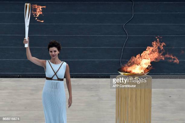 Actress Katerina Lechou playing a high priestess holds a torch at The Panathenaic Stadium in Athens on October 31 during the handover ceremony of the...
