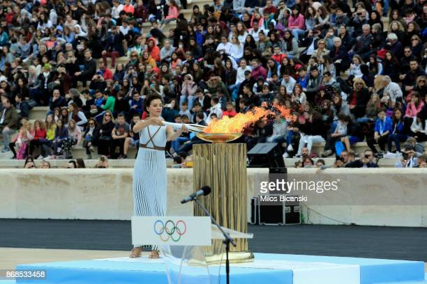 Actress Katerina Lechou playing a high priestess lights a torch at The Panathenaic Stadium during the handover ceremony of the Olympic flame for the...