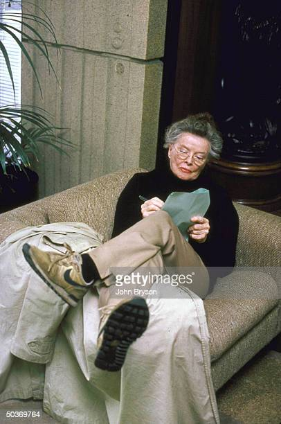 Actress Katharine Hepburn on couch writing on papers in lap for book about making the move African Queen
