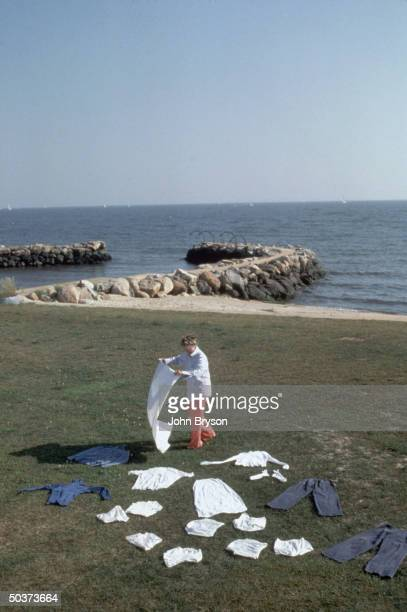 Actress Katharine Hepburn setting laundry out to dry on lawn of her home w shoreline water and rocks visible in bkgrd