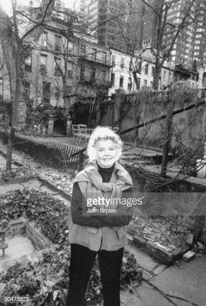 Actress Katharine Hepburn standing in the courtyard of her townhouse
