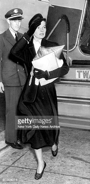 Actress Katharine Hepburn the Hollywood screen star makes another of her flying trips to the Big Town Carrying heaps in her arm she hurries from...