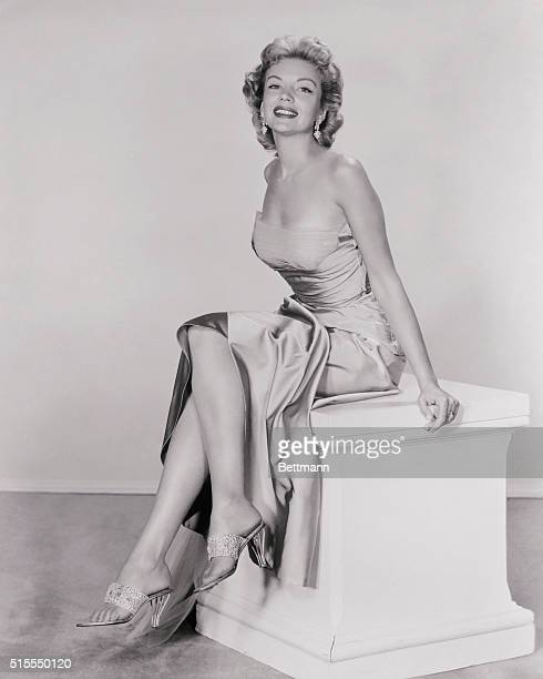 Actress Kathleen Hughes who starred in Dawn At Socorro has the ideal set of gams to go with the world's most expensive shoes which she is shown...