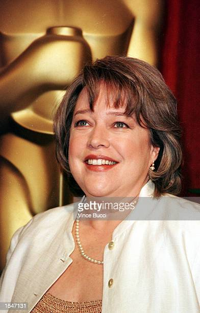 Actress Kathy Bates poses with a large Oscar statue March 8 1999 in Beverly Hills at the annual Oscar nominees luncheon hosted by the Academy of...