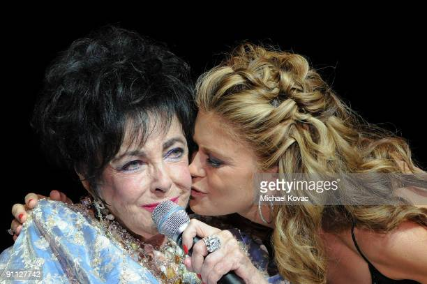 Actress Kathy Ireland kisses Elizabeth Taylor during the 27th Annual Macy's Passport Fashion Show Benefit at Barker Hanger on September 24 2009 in...