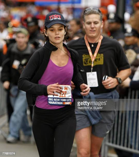 US actress Katie Holmes crosses the finish line and runs to her husband Tom Cruise and daughter Suri after she completed the New York City Marathon...