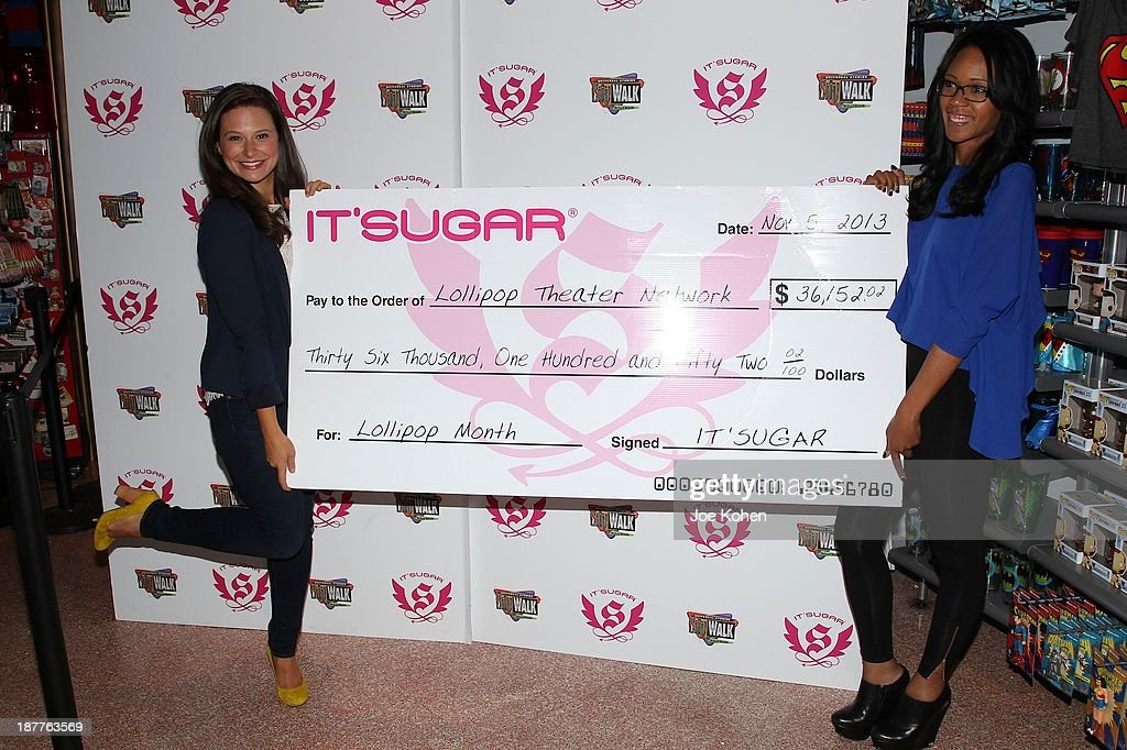Actress Katie Lowes and Veronica Flournoy attend IT'SUGAR check presentation to Lollipop Theater network at IT'SUGAR Universal CityWalk at Universal CityWalk on November 11, 2013 in Universal City, California.