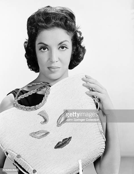 Actress Katy Jurado shows off a purse embroidered with a stylized face