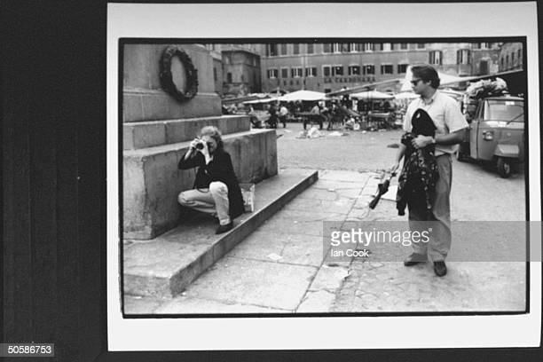 Actress Kelly Curtis squatting while shooting picture at Campo dei Fiori while husband Scott Morfee watches holds her things La Carbonara restaurant...