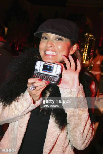 Actress Kelly Hu poses with the new V LG cell phone during the 100th issue Maxim magazine party at the Wynn Resort in Las Vegas Nevada on April 07...