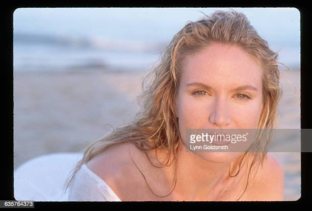 1989 Actress Kelly Lynch is shown on a beach in this head and shoulders photo She wears a sheer white dress