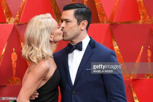 Actress Kelly Ripa and her husband Mark Consuelos kiss as they arrive for the 90th Annual Academy Awards on March 4 in Hollywood, California. / AFP...
