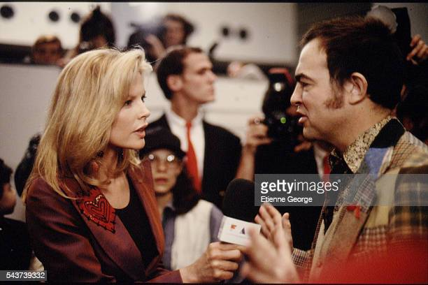 Actress Kim Basinger and French fashion designer Christian Lacroix on the set of the film PrêtàPorter directed by American director Robert Altman